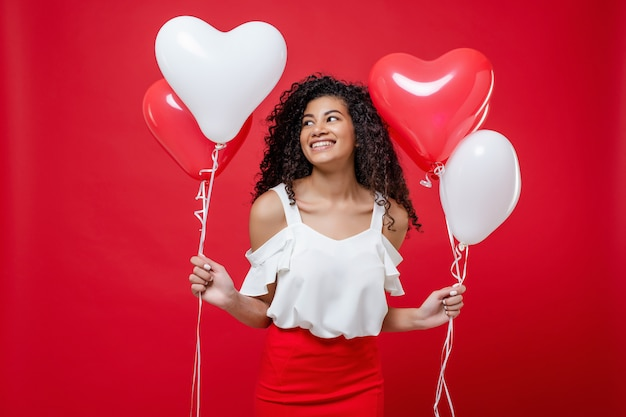 Happy smiling african girl holding colorful helium balloons isolated on red