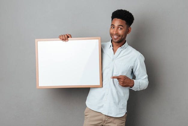 Happy smiling african man pointing finger at blank board