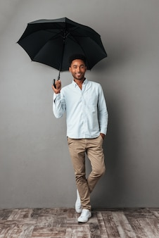 Happy smiling african man standing with open umbrella