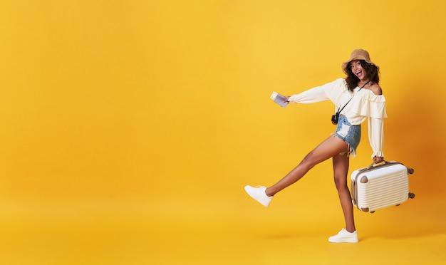 Счастливая усмехаясь африканская женщина одела в одеждах лета с багажом наслаждаясь их убежищем летних каникулов в желтом цвете с космосом экземпляра.