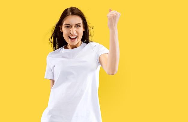 幸せな笑顔とお祝いの女の子。黄色の壁に分離された美しい女性の半分の長さの肖像画。若い笑顔の女性。ネガティブスペース。顔の表情、人間の感情の概念。