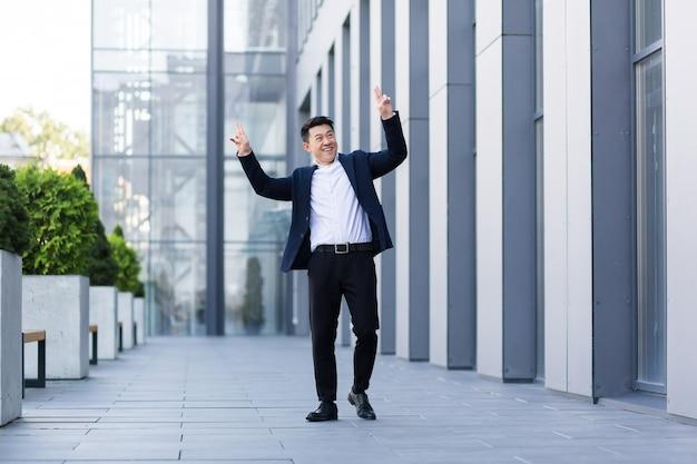 행복한 미소와 성공적인 아시아 사업가가 그의 일의 기쁨과 좋은 결과로 춤을 춥니다