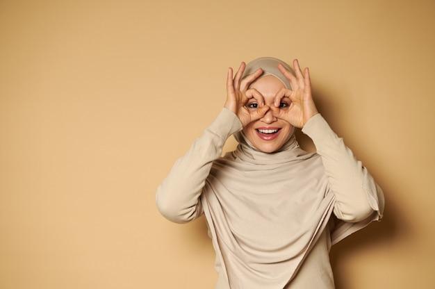 良いジェスチャーで彼女の指を通して正面を見てヒジャーブで覆われた頭を持つ幸せな笑顔のアラブの女性
