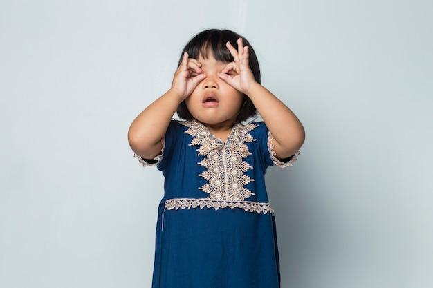 幸せな笑顔のアジアの子の女の子が白い背景で孤立して見える変な顔を作る