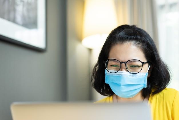検疫中に人と会うためのラップトップコンピューターでオンラインビデオ通話を楽しんで楽しんでいるメガネで幸せな笑顔のアジアの女性フリーランサーの摩耗