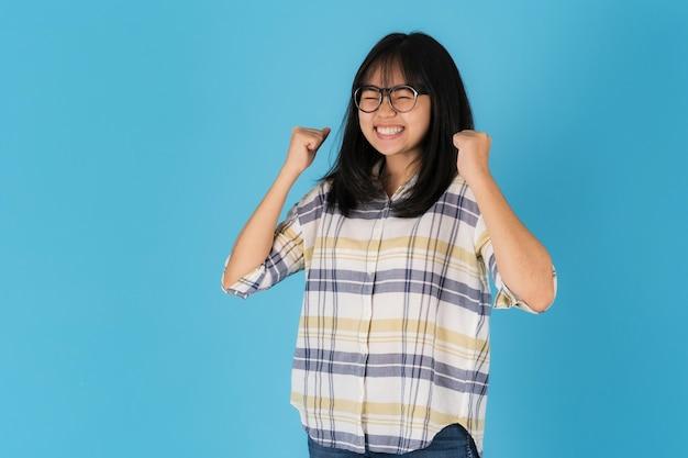 Счастливая улыбающаяся азиатская девушка, стоящая на синем фоне