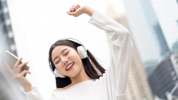 Happy smiling asian girl wearing headphones listening and moving to the music against city building wall