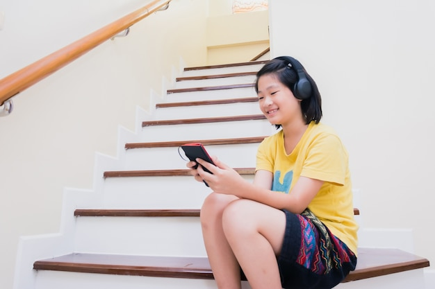 Happy smiling asian kids on ladder listening to music from smart phone with earphone, technology con