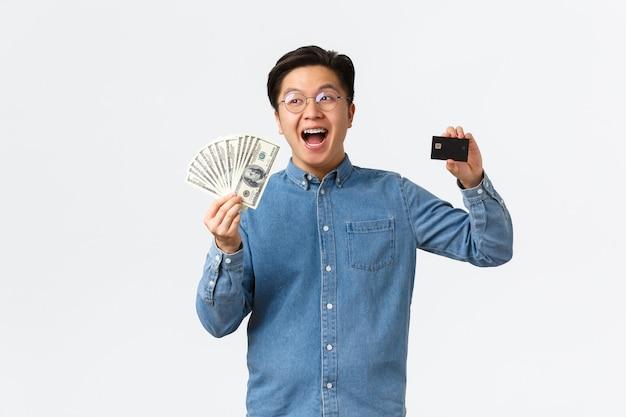 Uomo asiatico sorridente felice con bretelle e occhiali che ride allegramente e mostra la carta di credito in possesso ...