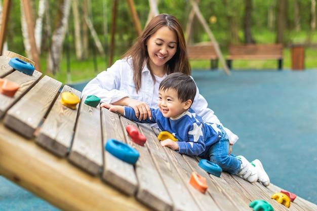 幸せな笑顔のアジアの母と子は、夏の公園の遊び場で遊んでいます。テキスト用のスペースをコピーする