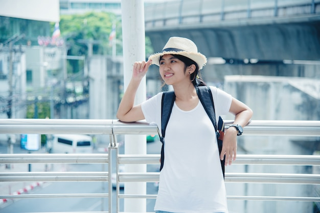 Happy smiling asian student girl with backpack at city background