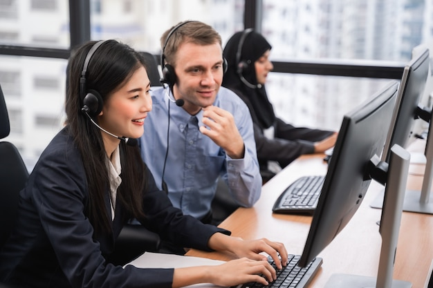 Happy smiling asian woman call center and operator with colleague wearing headsets working on computer and talking with customer with her service mind