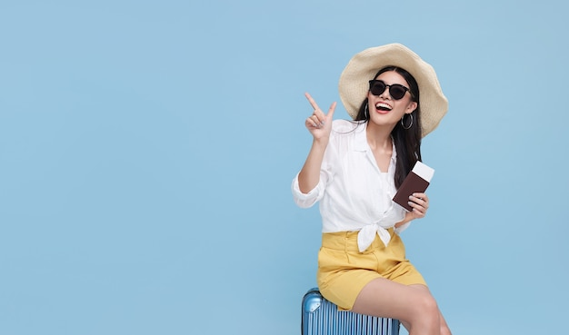 Счастливая улыбающаяся азиатская женщина, одетая в летнюю одежду и шляпу с багажом, наслаждаясь летними каникулами и указывая пальцем на копию пространства на ярко-синем фоне.
