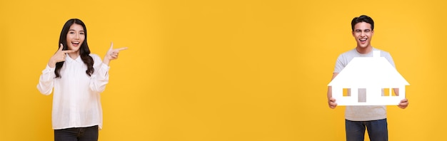 Счастливая улыбающаяся азиатская женщина его палец указывает на человека, держащего бумажный дом, изолированный на желтом фоне с копией пространства. панорамный фон.
