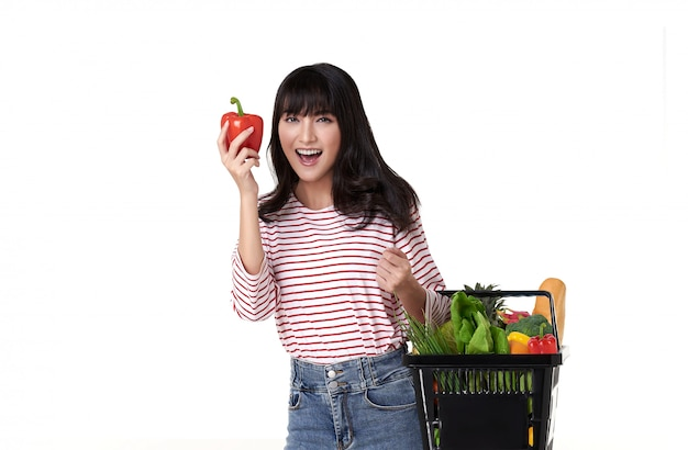 Счастливая усмехаясь азиатская женщина держа покупки корзины полный овощей изолированных на белой предпосылке.