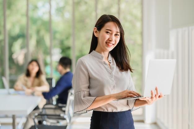 Счастливая улыбающаяся азиатская женщина, держащая ноутбук с коллегой