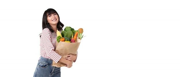 Счастливая усмехаясь азиатская женщина держа бумажную хозяйственную сумку полный овощей изолированных на предпосылке знамени с космосом экземпляра.