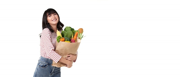 Happy smiling asian woman holding paper shopping bag full of vegetables isolated on banner background with copy space.