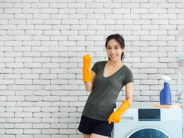 Счастливая улыбающаяся азиатская женщина, домохозяйка в резиновых перчатках поднимает кулак в победном жесте и празднует успех возле стиральной машины на кирпичной стене