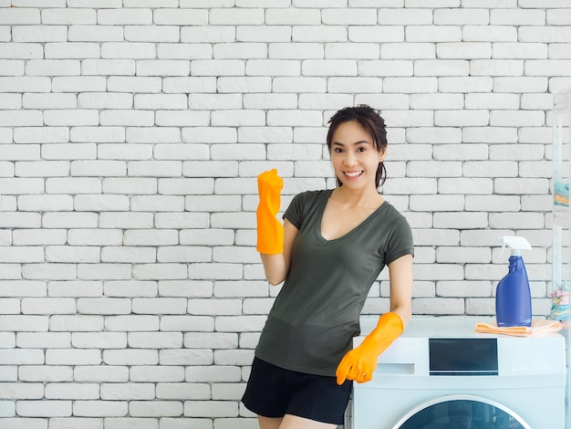 Happy smiling asian woman, housewife wearing rubber gloves raising fist in winning gesture and celebrating success near washing machine on brick wall