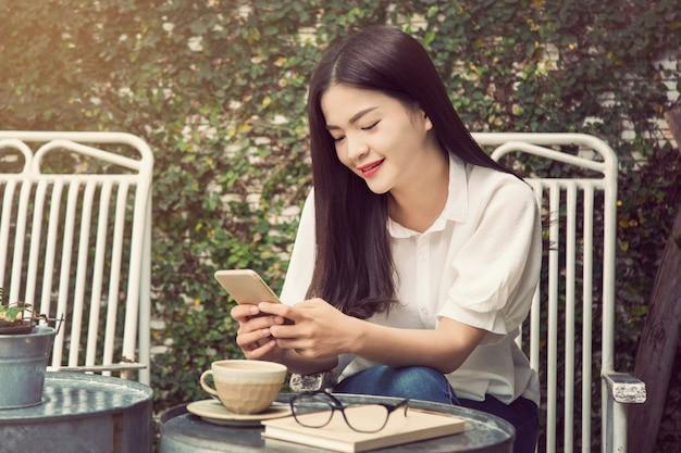 ソーシャルメディアで友人とつながるために彼女の電話を使っている笑顔のアジア人女性