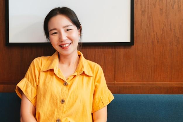 黄色のシャツを着て、モダンなカフェに座って幸せな笑顔のアジア女性。