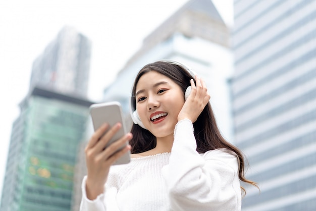 Happy smiling asian woman wearing headphones and looking at smartphone while listening to streaming music against city building wall