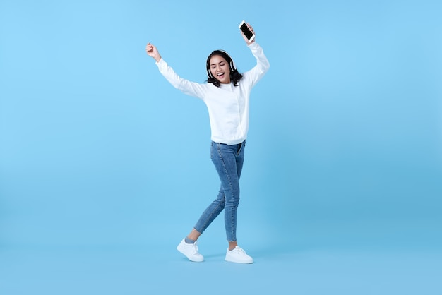 Happy smiling asian woman wearing wireless headphones listening to music and dancing on blue.