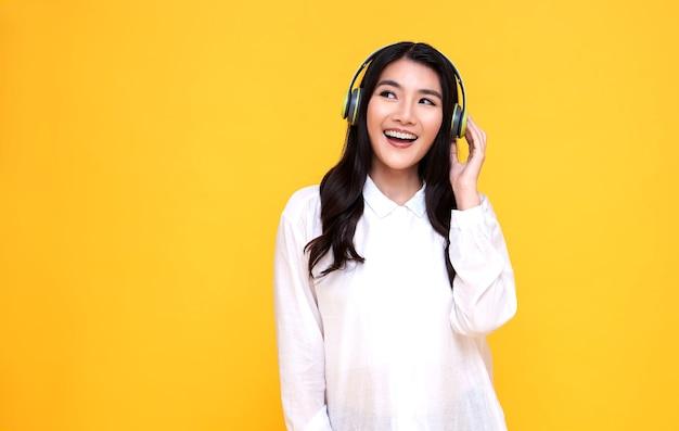 Счастливая улыбающаяся азиатская женщина в беспроводных наушниках, слушающая музыку на желтом фоне.