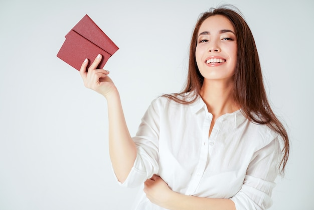 Happy smiling asian young long hair woman with two passports on white background isolated