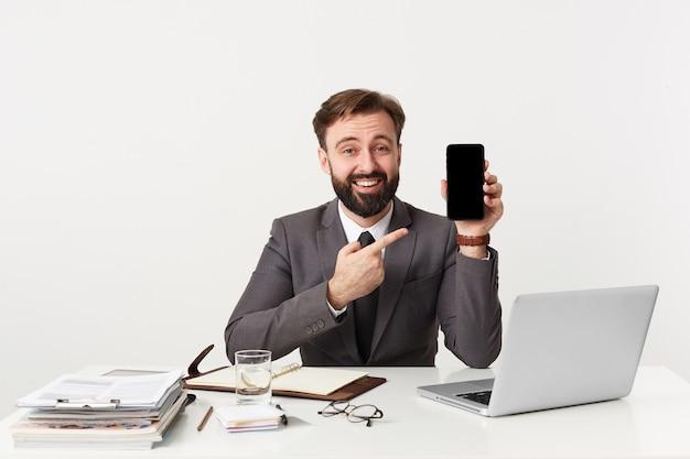 幸せな笑顔の魅力的なひげを生やしたビジネスマン、オフィスのデスクトップに座って、カメラを見て、ネクタイで高価なスーツを着て、彼のスマートフォンを指で指しています。