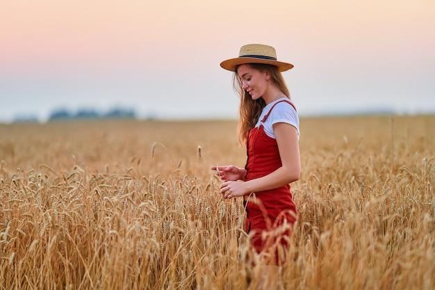Счастливая улыбающаяся привлекательная милая свободная молодая женщина в соломенной шляпе и джинсовом комбинезоне, стоящая одна в золотисто-желтом пшеничном поле и наслаждающаяся прекрасной жизнью в момент свободы в летнее время