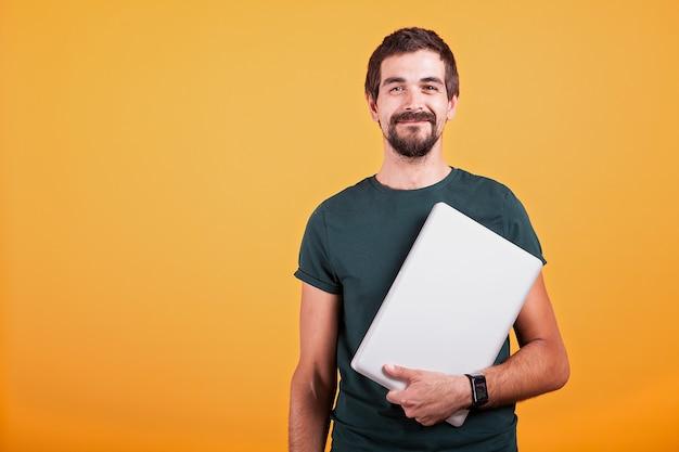 오렌지 배경에 고립 된 그의 손에 노트북과 함께 행복 하 게 웃는 매력적인 남자. 통신을 위한 무선 기술