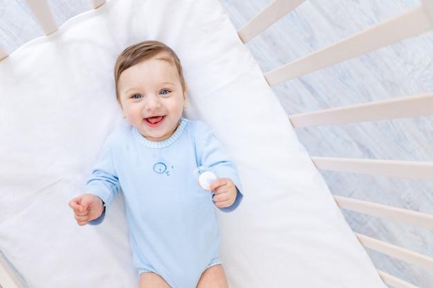 Счастливый улыбающийся мальчик в кроватке в синем боди, милый радостный малыш в спальне