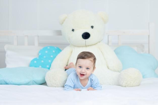 파란색 바디 슈트에 큰 테디 베어, 침실에 귀여운 작은 아기와 함께 침대에 행복 웃는 아기