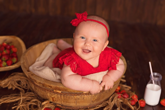 Happy smiling baby girl in a red dress lies on her stomach and eats strawberries and drinks milk