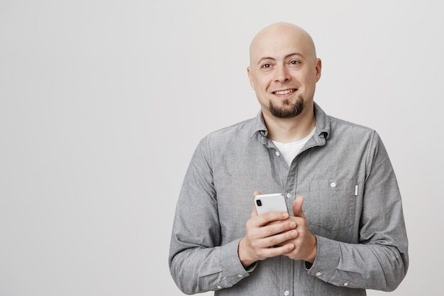 Happy smiling bald adult man look aside, holding smartphone