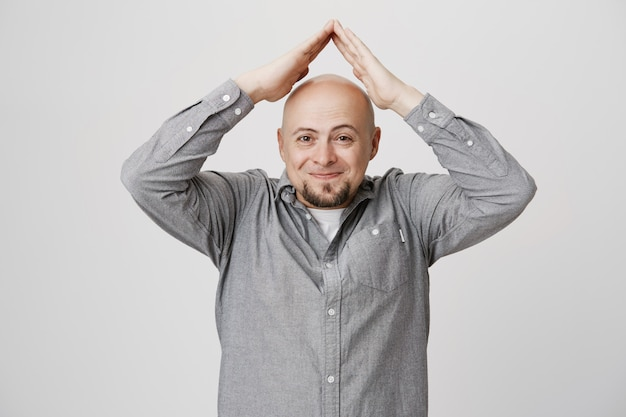 Happy smiling bald man showing roof gesture