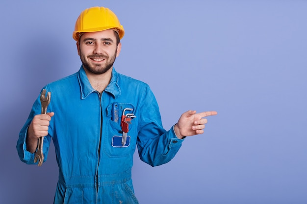 Happy and smiling bearded engineer with wrench tool in hand and pointing aside with index finger while stands against