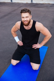 Happy smiling bearded fitness man doing workout on blue mat outdoors