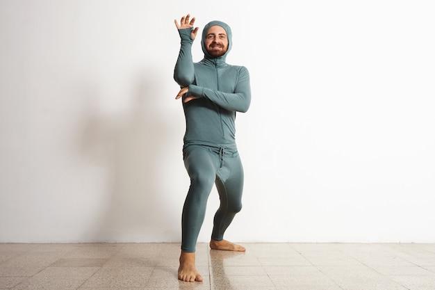 スノーボードサーマルベースレイヤースイートを身に着け、忍者のようにポーズをとって、白で隔離の幸せな笑顔のひげを生やしたフィット男性