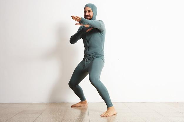 Felice sorridente barbuto maschio montato che indossa snowboard termico baselayer suite di lana merino e si comporta come un ninja in posizione di difesa, isolato su bianco