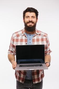 白い壁に分離された空白の画面のラップトップコンピューターを保持している幸せな笑顔のひげを生やした男