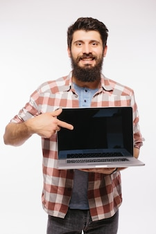 Happy smiling bearded man holding blank screen laptop computer isolated over white wall
