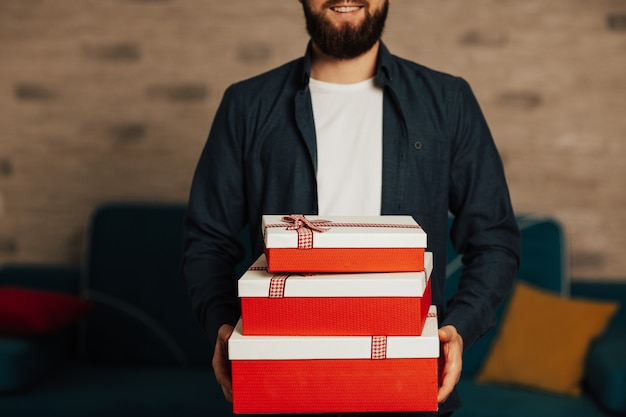 Счастливый улыбающийся бородатый мужчина держит в руках подарки. портрет возбужденного молодого человека, держащего много подарков в красных коробках.