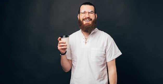 수염이 난 행복한 미소를 짓고 있는 남자가 테이크 아웃 컵을 들고 있습니다.