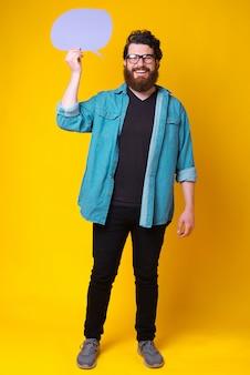 Счастливый улыбающийся бородатый человек улыбается на камеру и проведение речи пузырь фиолетовый