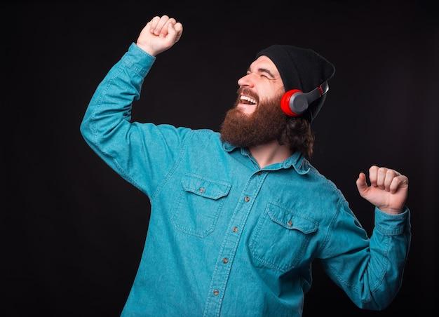 Счастливый улыбающийся бородатый мужчина слушает музыку в беспроводных наушниках и танцует над темной стеной