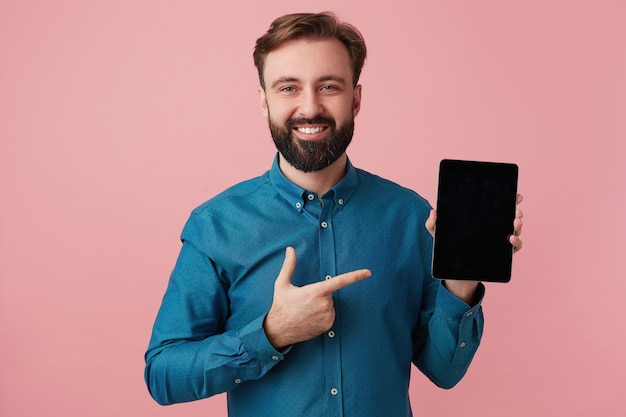 Happy smiling bearded man wants to draw your attention, pointing with finger to his device. looking at camera in surprise isolated over pink background.