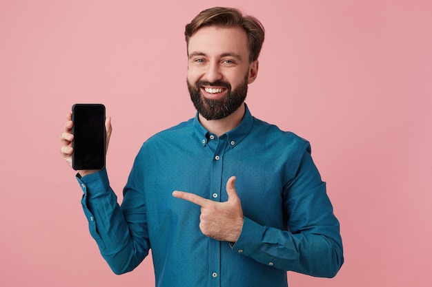 Happy smiling bearded man wants to draw your attention, pointing with finger to his smarthpone, wearing a denim shirt. looking at camera in surprise isolated over pink background.